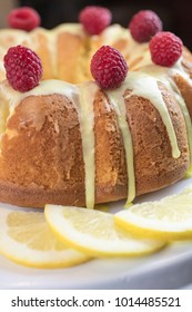 Lemon cake frosted with yellow sugar icing and red raspberries, dressed with lemon slices on the side on a white platter