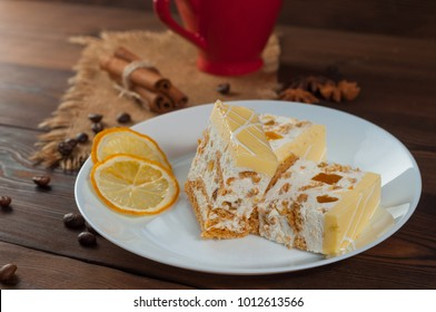 Lemon cake on a plate with dried lemon on a wooden table