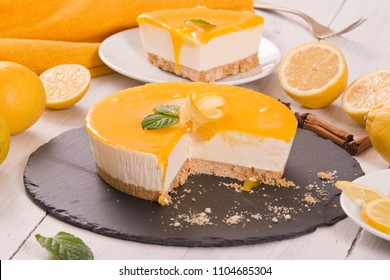 Lemon cheesecake on black dish.