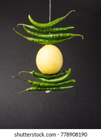 Lemon Chilies tied with thread and tied for hanging on doors at home OR shop to avoid any bad fortune also known as totka or nazar battuLemon Chilies tied with thread and tied for hanging on doors at