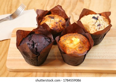 Lemon And Chocolate Muffins In Paper Cupcake Holder On Wooden Table