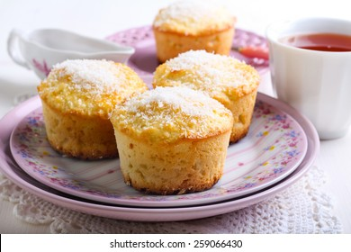 Lemon and coconut cakes on plate and cup of tea