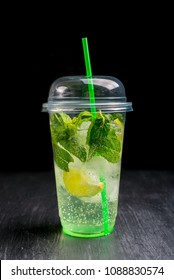 Lemon coctail drink. Lemonade in one plastic cup and lemon with mint on the table