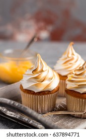 Lemon cup cakes with cream on a gray background