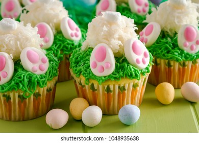 Lemon cupcakes filled with fresh lemon curd decorated with spring green grass and Easter bunny butt and feet sitting a green wood