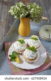 Lemon cupcakes and and a vase with Hydrangea on a metal tray