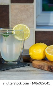 Lemon drink. Authentic glass of home-made lemonade. Refreshing summer beverage. Easy cool healthy drink with fresh organic lemons and mint. Home made.