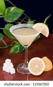 Lemon drop martini served on a bar top with fresh lemons and sugar cubes, garnish with a lemon slice and sugar rim