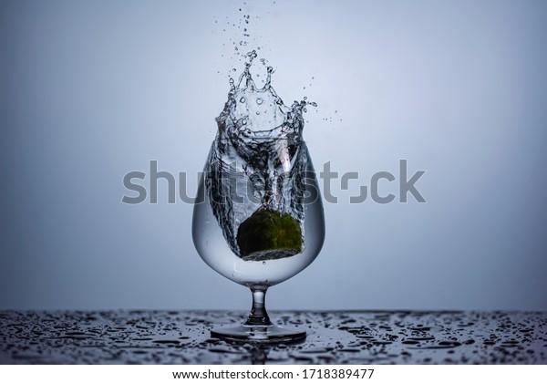 Lemon drops water splash on wine glass high speed photography