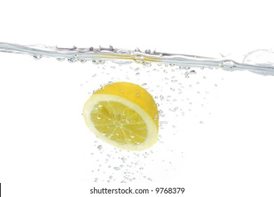 Lemon in the flight surrounded and followed by water bubbles