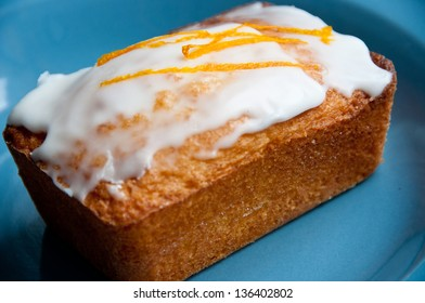 A lemon frosted almond cake sits on a blue plate. The cake is topped with a thin strip of lemon rind.