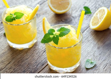 Lemon Frozen Granita Slush Drink in glasses on rustic wooden table. Homemade Italian Granita Dessert, refreshing summer Slush Drink.