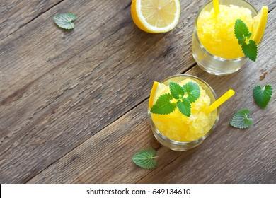 Lemon Frozen Granita Slush Drink in glasses on rustic wooden table. Homemade Italian Granita Dessert, refreshing summer Slush Drink.