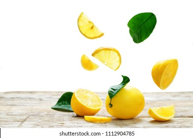 Lemon Fruit with flying slices on a wood table isolated. tinting. selective focus