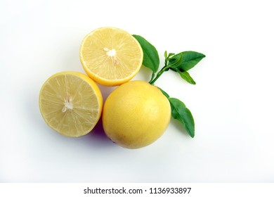 Lemon fruit with half and leaves isolated on white