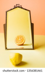 Lemon fruit reflecting as an orange on a mirror in a colored environemnt, conceptual image for the theme of changing , thinking difference, getting another pern