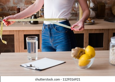 lemon and ginger detox diet for weight loss. slim and fit body. woman measuring her waist with a tape