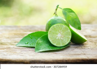 lemon with green leafs on wood background