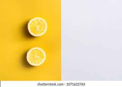 Lemon halves on split color, yellow and white background with copy space for text.
