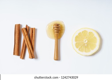 lemon, honey and cinnamon sticks on white background, food combination concept
