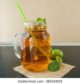 Lemon ice tea on black wooden table, green mint, green lemons,