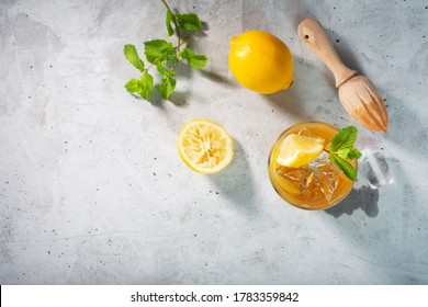 Lemon ice tea on concrete gray background with mint and ice, nice drink for summer hot season, top view