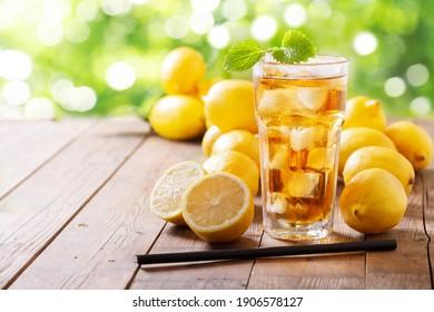 Lemon iced tea with fresh fruits on a wooden table
