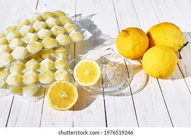 Lemon juice ice cubes with lemons on white wooden table. Frozen lemon juice preservation. Different ways to use lemon.