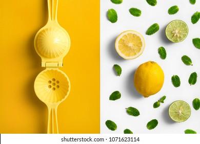 Lemon juicer. hand press, on split colored background with lemon lime and mint leaves.