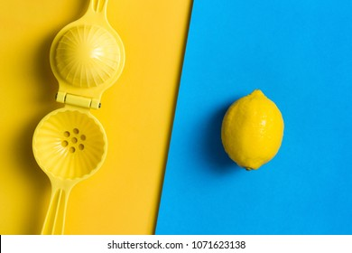Lemon and juicer, squeezer on contrasting colored background.