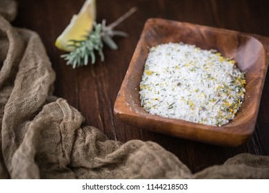 Lemon Lavender Herb Salt in Small Wooden Bowl; Fresh sprig of herb on Wooden Tabletop beside the bowl