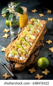 Lemon and lime curd meringue tart decorated with lime slices and biscuits on the dark background