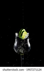 lemon lime falling into glass with water and black background, splash motion effect
