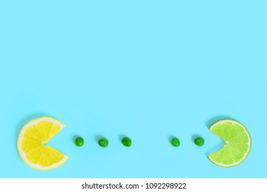 Lemon and lime fruits eating green peas on creative color paper background. Trendy minimal pop art style. Concept of funny colorful food.