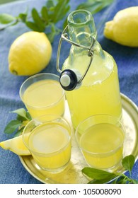 Lemon liqour (limoncello) in glass on natural background. Selective focus