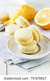 Lemon Macarons with lemon curd, lemon, piping bag on a white wooden table