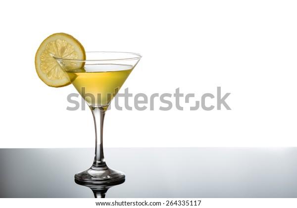 lemon martini on reflective table with lemon slice