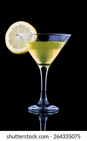 lemon martini with lemon slice on black background