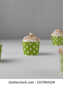 Lemon meringue cupcakes in a green cupcake case, lemon meringue, toasted meringue, Christmas cupcakes, green cupcake cups, cupcake on a white surface, minimalist cupcake photography