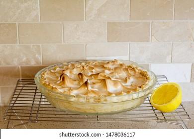 Lemon Meringue Pie with lemon half on a cooling rack with tile background; fresh homemade lemon meringue pie