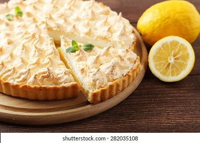 Lemon meringue pie on cutting board on brown wooden background