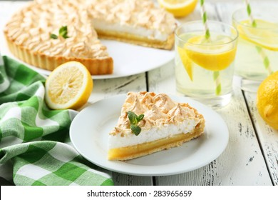 Lemon meringue pie on plate on white wooden background