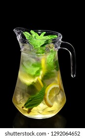 Lemon and mint cold lemonade in pitcher isolated on black background