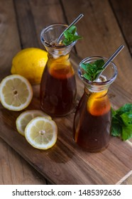 Lemon and mint iced tea in glass carafes with mint and lemon pieces on wood board