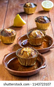 Lemon muffins in golden cases on wooden table board