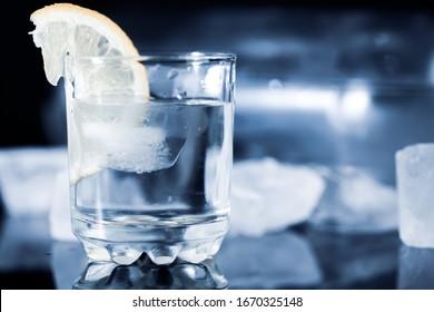 lemon on vodka of glass and bottle on table
