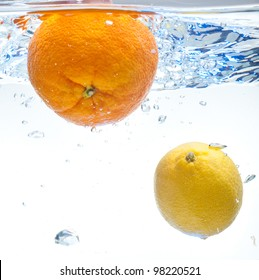 Lemon and orange floating in the water on a white background