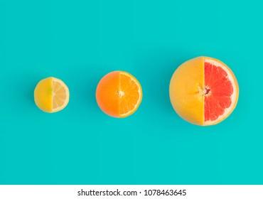 Lemon, orange and red grapefruit on bright blue background. Minimal flat lay concept.