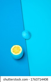 Lemon painted cyan on the outside on a blue background. Sliced lemon above view. Contrasting colors with lemon yellow, blue, and cyan. Citrus fruit with a blue peel