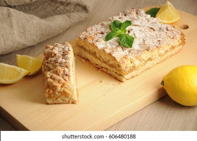 The lemon pie with fresh lemons and mint on wooden, home made cake concept